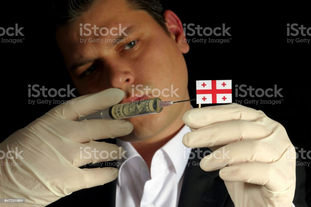 Young businessman gives a financial injection to Georgian flag isolated on black background stock photo