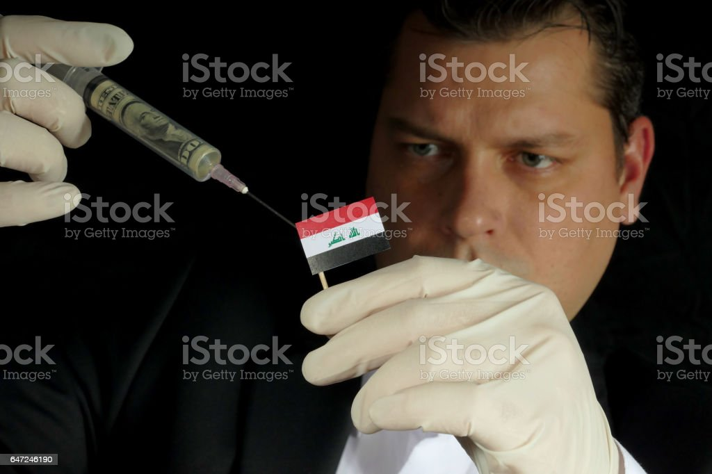 Young businessman gives a financial injection to Iraqi flag isolated on black background stock photo