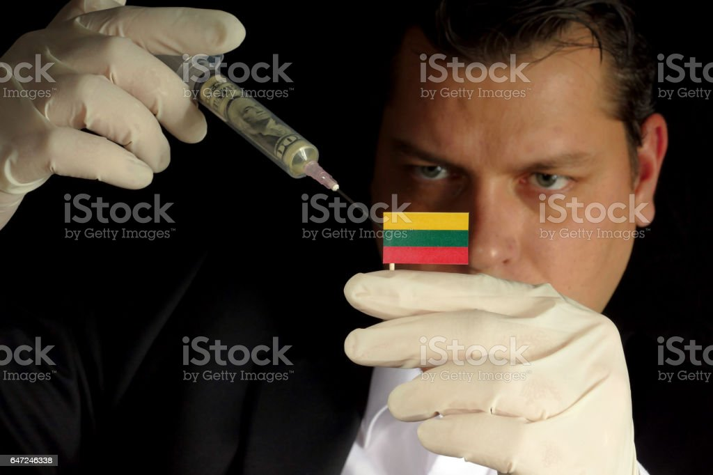 Young businessman gives a financial injection to Lithuanian flag isolated on black background stock photo