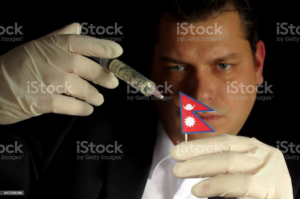 Young businessman gives a financial injection to Nepalese flag isolated on black background stock photo