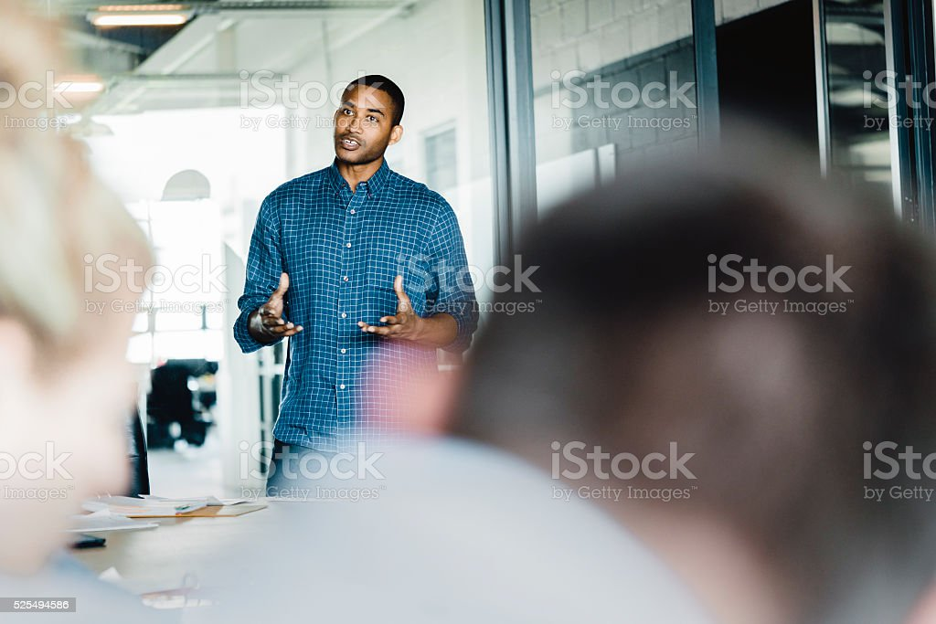 Young businessman giving presentation in office stock photo