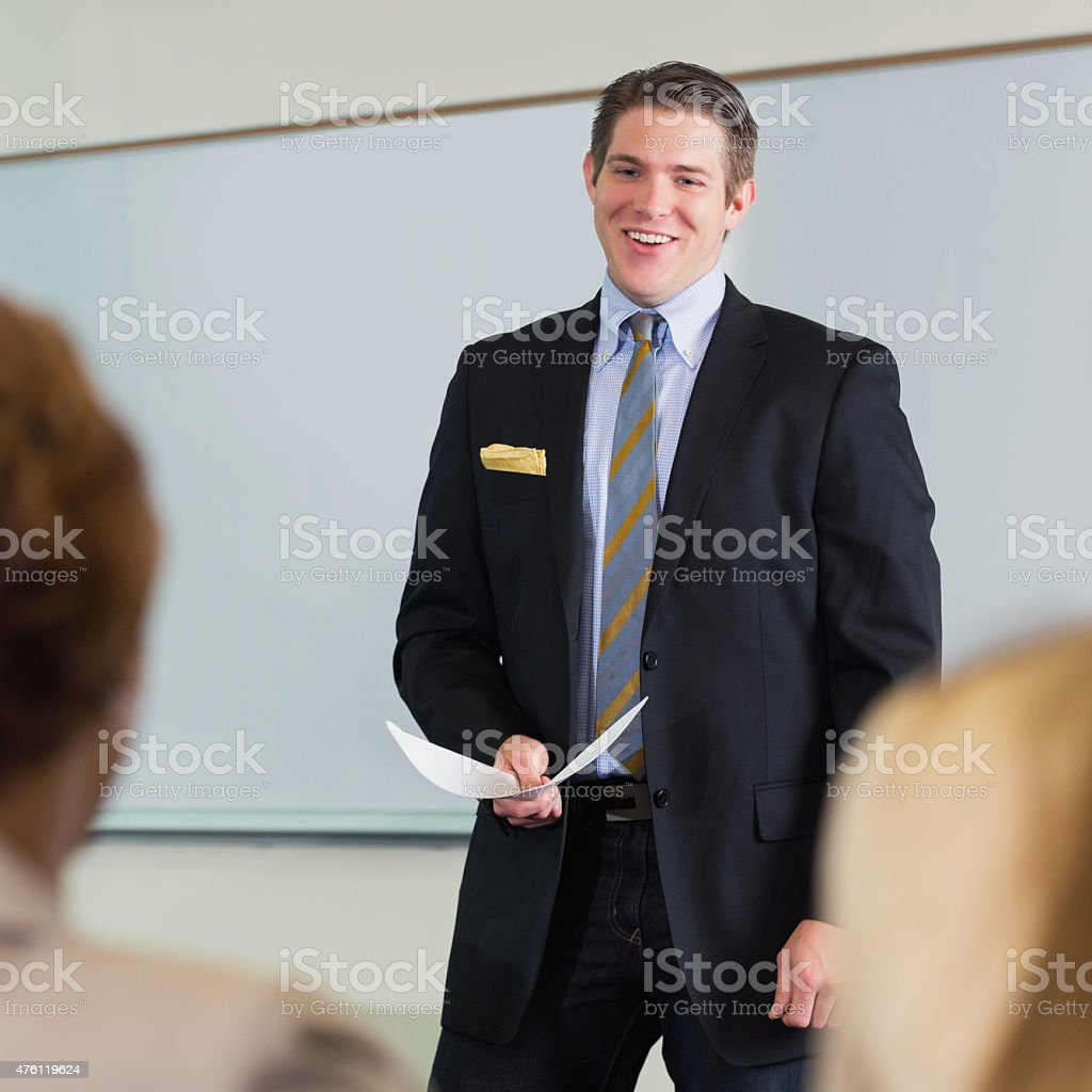 Young businessman giving speech or presentation during business seminar conference stock photo