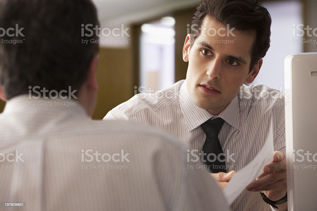 Young  Businessman going over report with older colleague stock photo