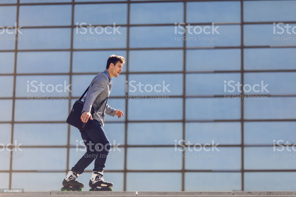Young businessman going to work on roller skates. stock photo