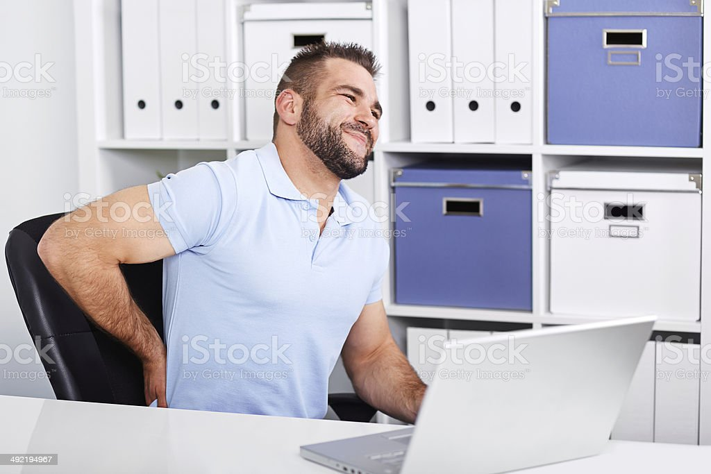 Young businessman has backache at work with a laptop stock photo