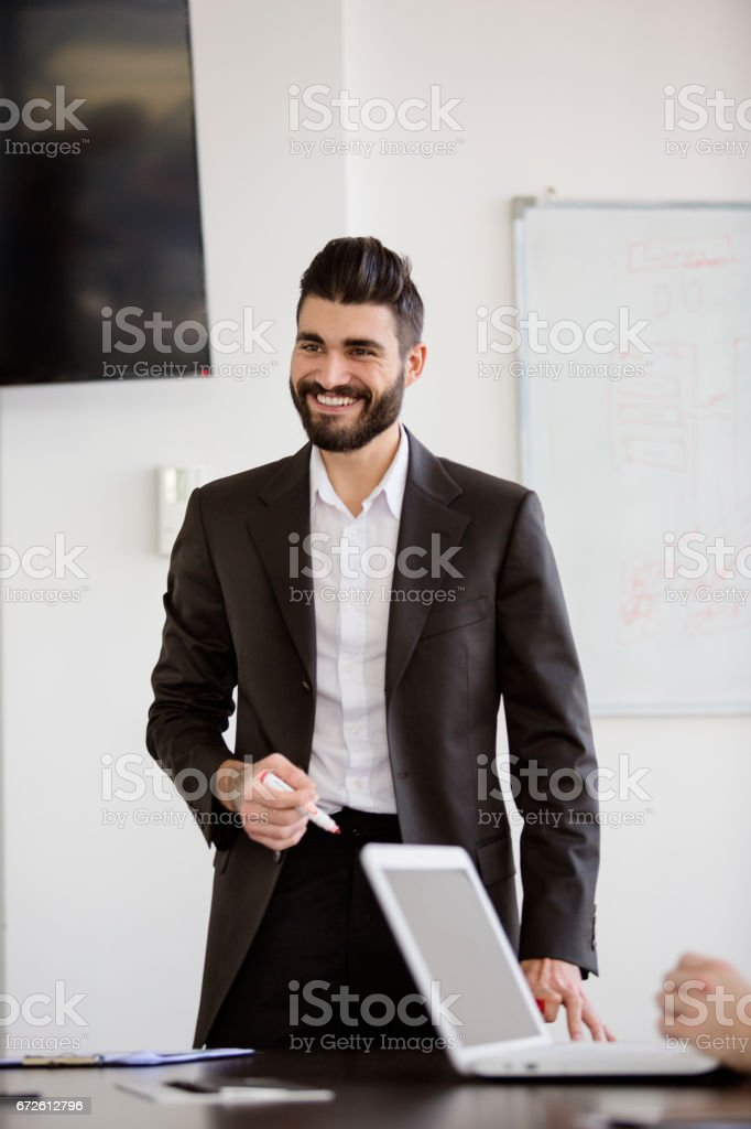 Young businessman holding a presentation in an office smiling. stock photo