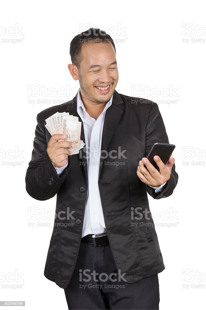 Young businessman holding banknote and cellphone stock photo