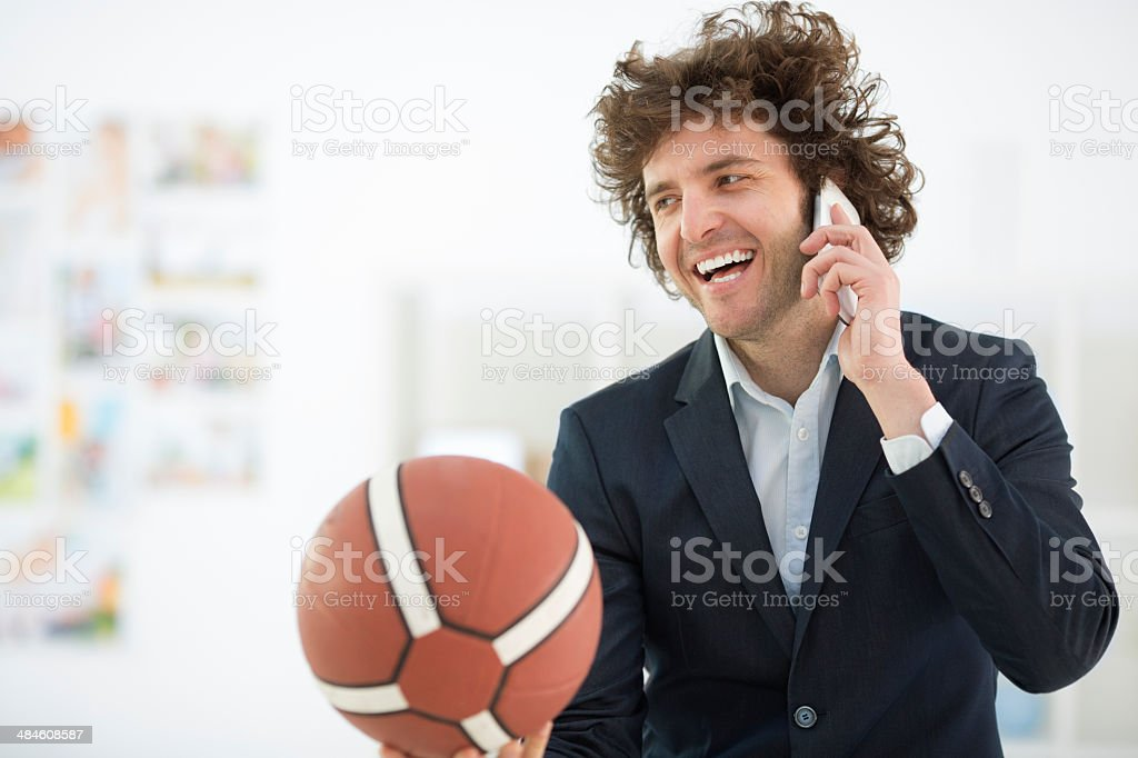 Young Businessman Holding Basketball Ball and talking on the phone. stock photo