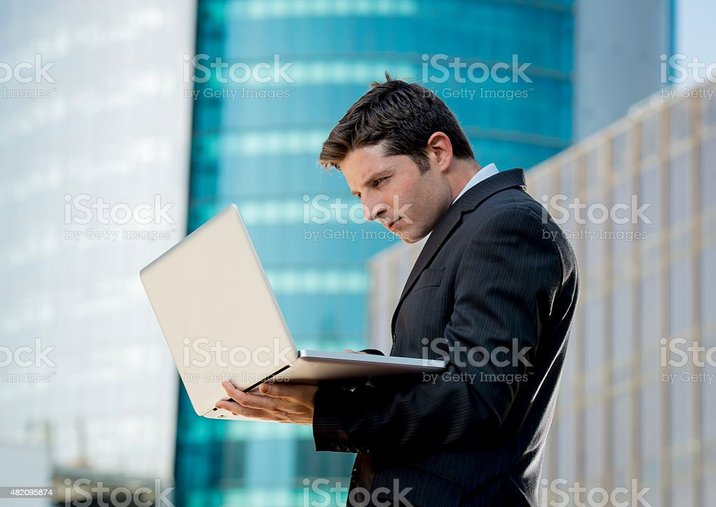 young businessman holding computer laptop working urban business outdoors stock photo