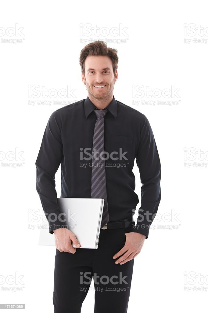 Young businessman holding laptop smiling royalty-free stock photo