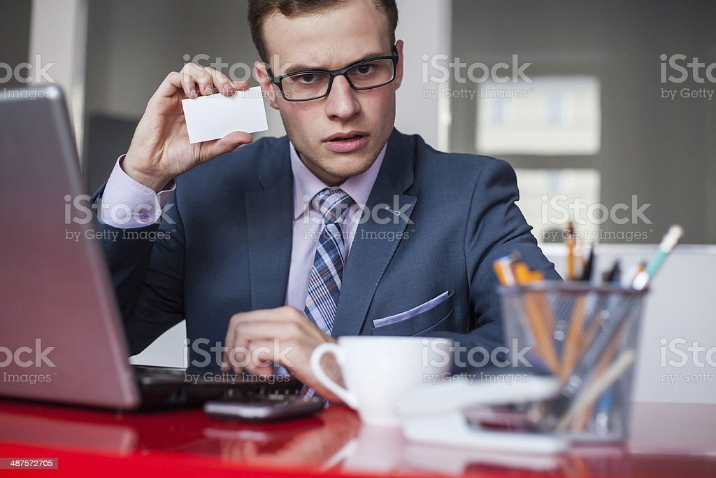 Young businessman holding mobile phone and white business card. stock photo