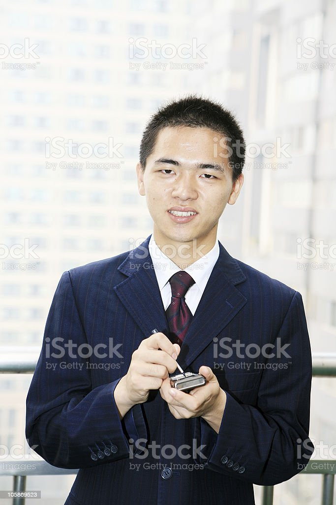 young businessman holding mobile phone royalty-free stock photo