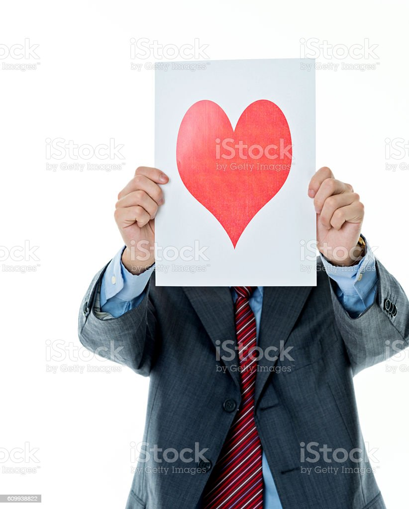 Young businessman holding up a paper with red heart stock photo