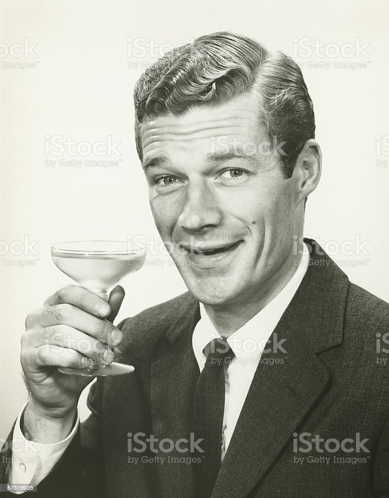 Young businessman holding wine glass, (B&W), portrait royalty-free stock photo