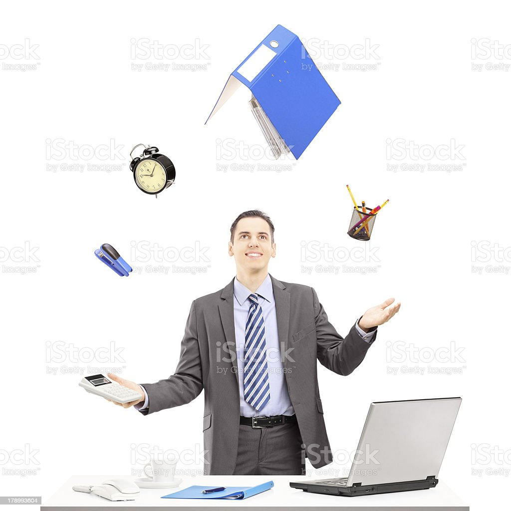 Young businessman in a suit juggling with office supplies stock photo
