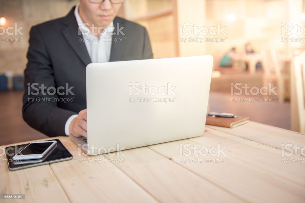 young businessman in black suit working with laptop for project management stock photo