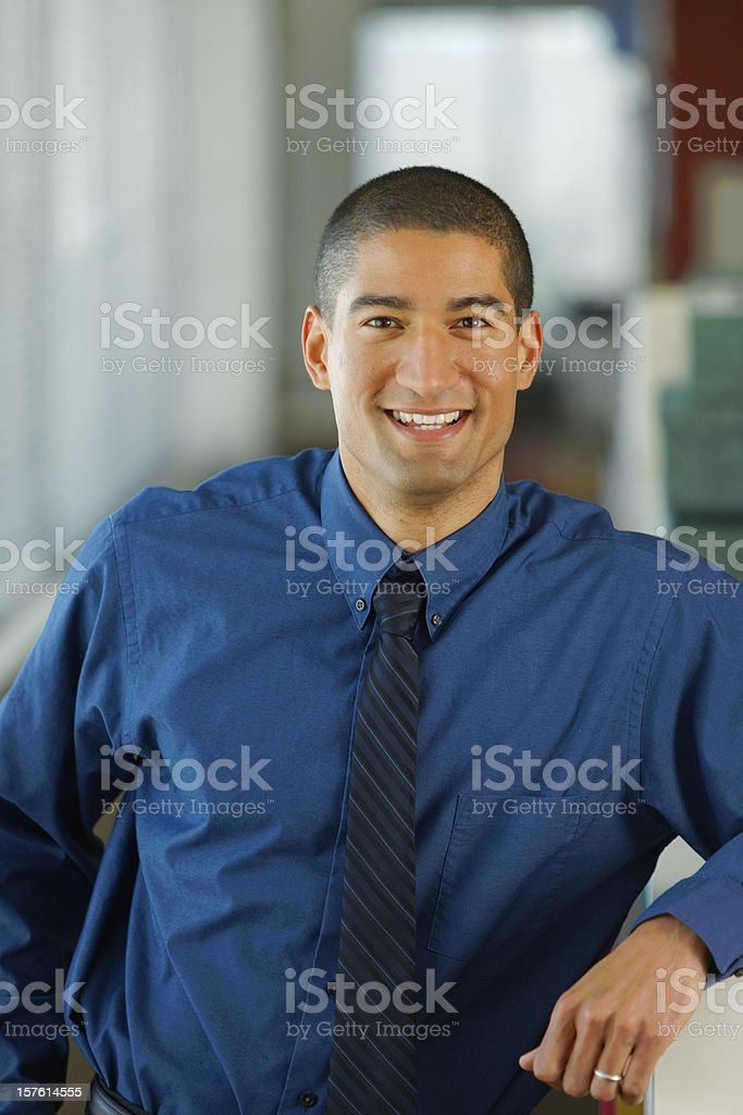 Young businessman in dark blue shirt smiling in his office royalty-free stock photo