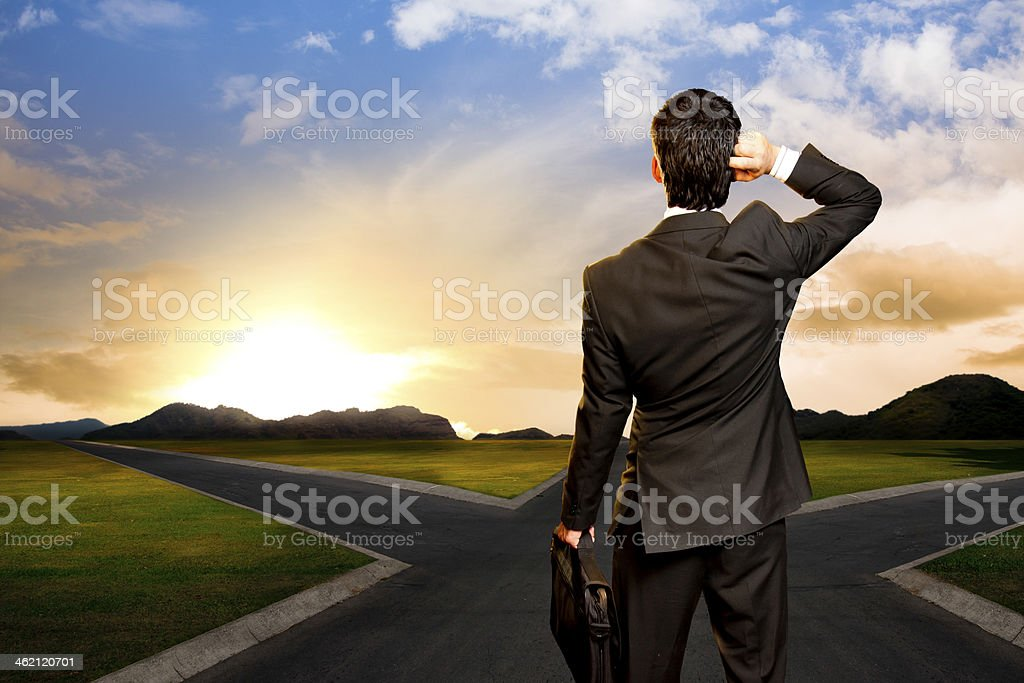 young businessman in front of a crossroad stock photo