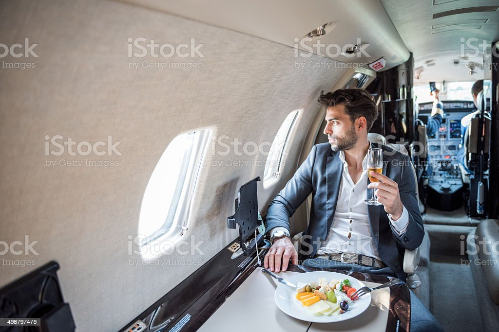 Young businessman in private jet airplane stock photo