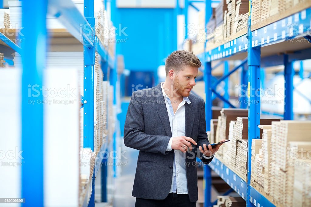 Young businessman in warehouse checking inventory stock photo
