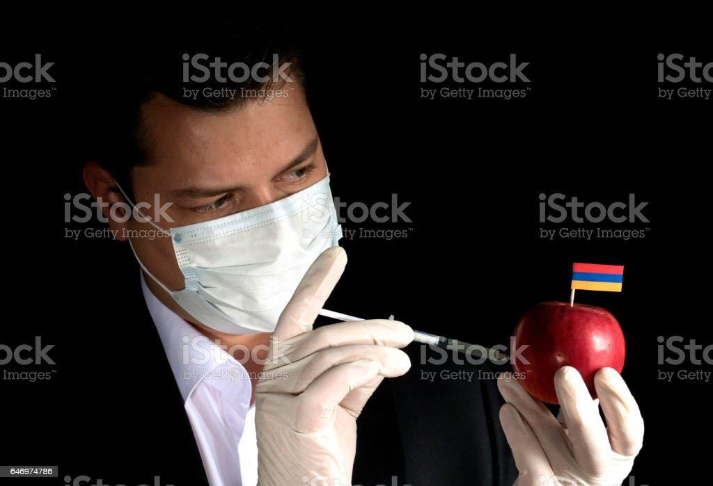 Young businessman injecting chemicals into an apple with Armenian flag on black background stock photo