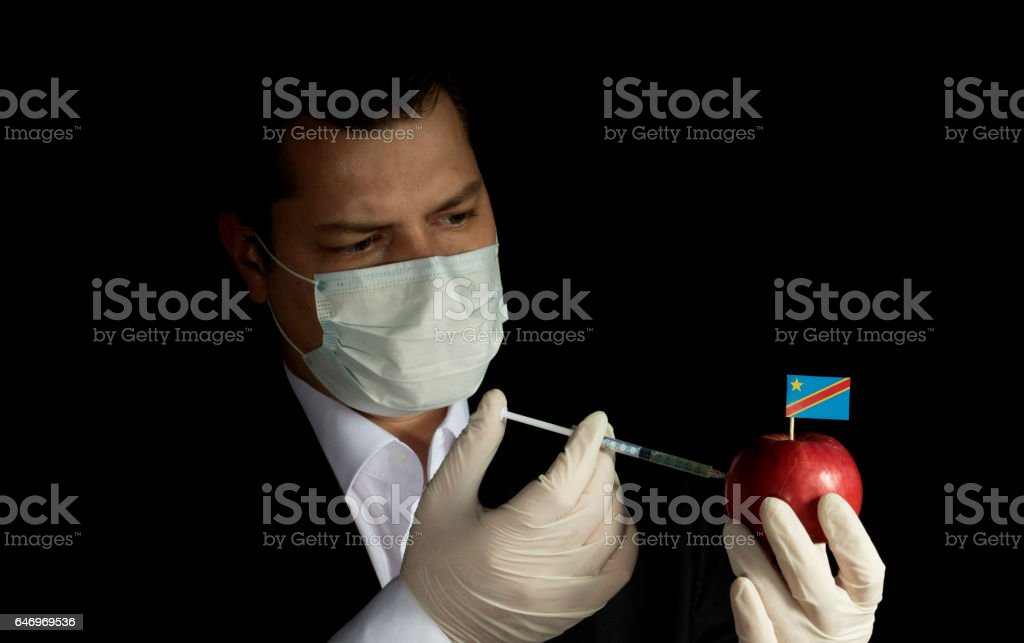 Young businessman injecting chemicals into an apple with Democratic Republic of Congo flag on black background stock photo