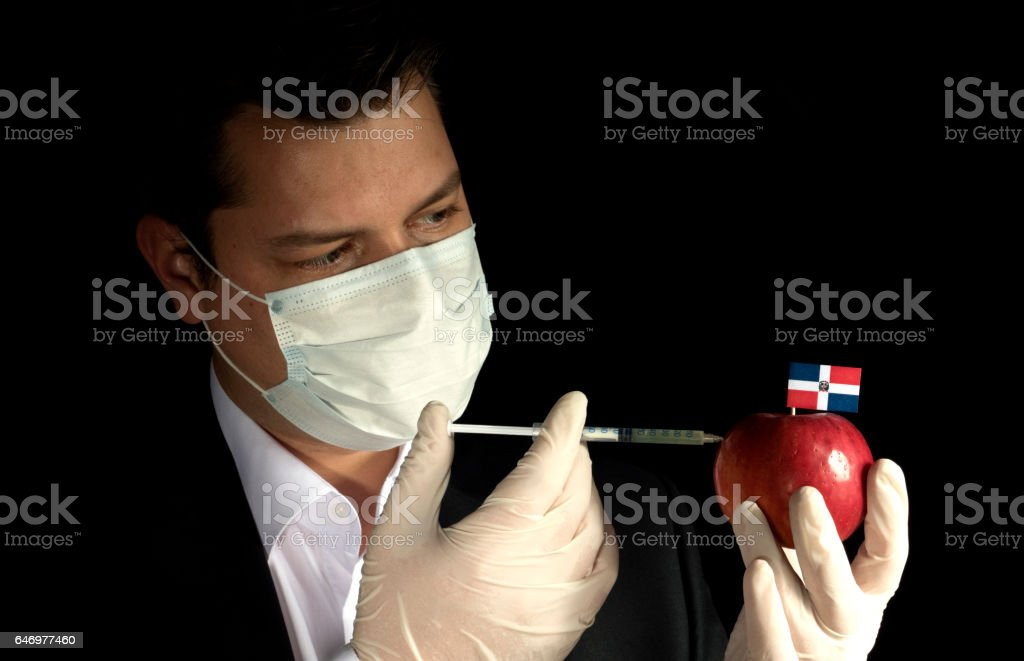 Young businessman injecting chemicals into an apple with Dominican Republic flag on black background stock photo