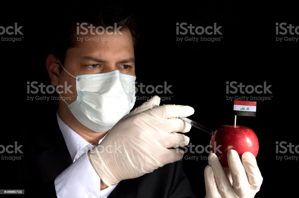 Young businessman injecting chemicals into an apple with Iraqi flag on black background stock photo