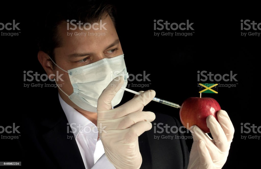 Young businessman injecting chemicals into an apple with Jamaican flag on black background stock photo