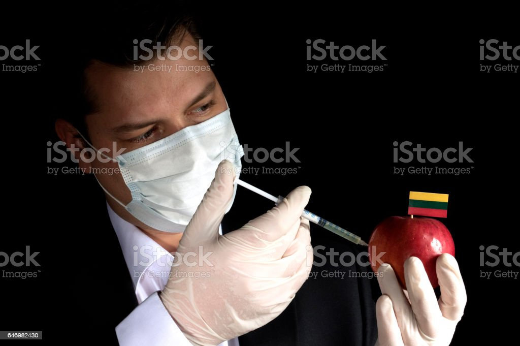 Young businessman injecting chemicals into an apple with Lithuanian flag on black background stock photo