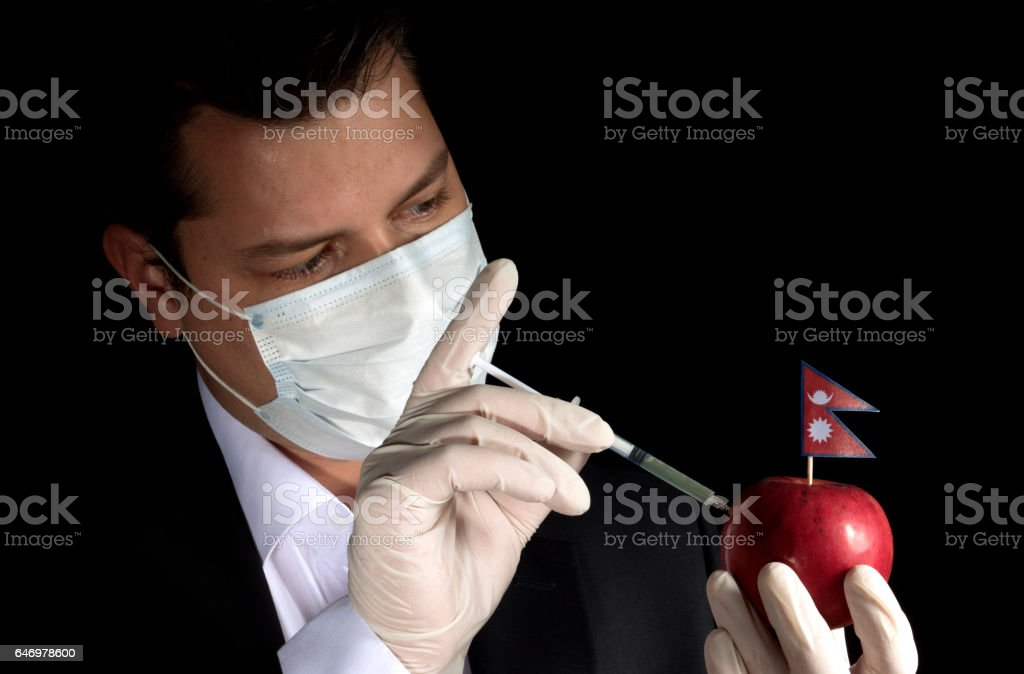 Young businessman injecting chemicals into an apple with Nepalese flag on black background stock photo