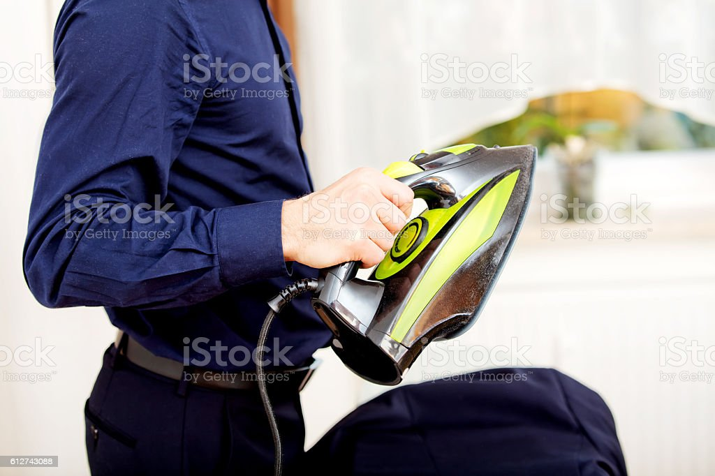 Young businessman ironing his jacket stock photo