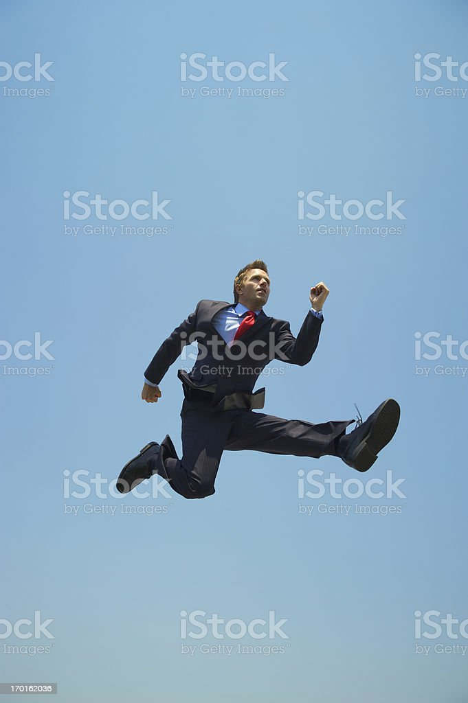 Young Businessman Jumping Outdoors High in Blue Sky royalty-free stock photo