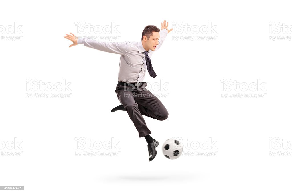 Young businessman kicking a football stock photo