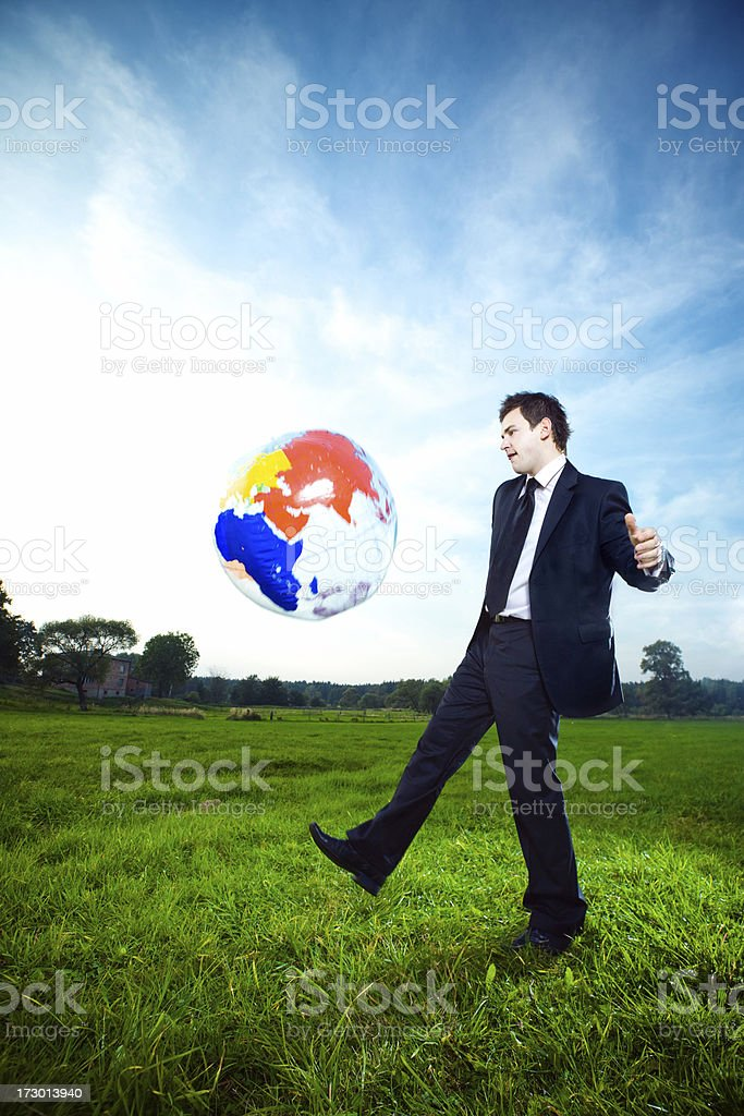 Young businessman kicking inflatable globe stock photo