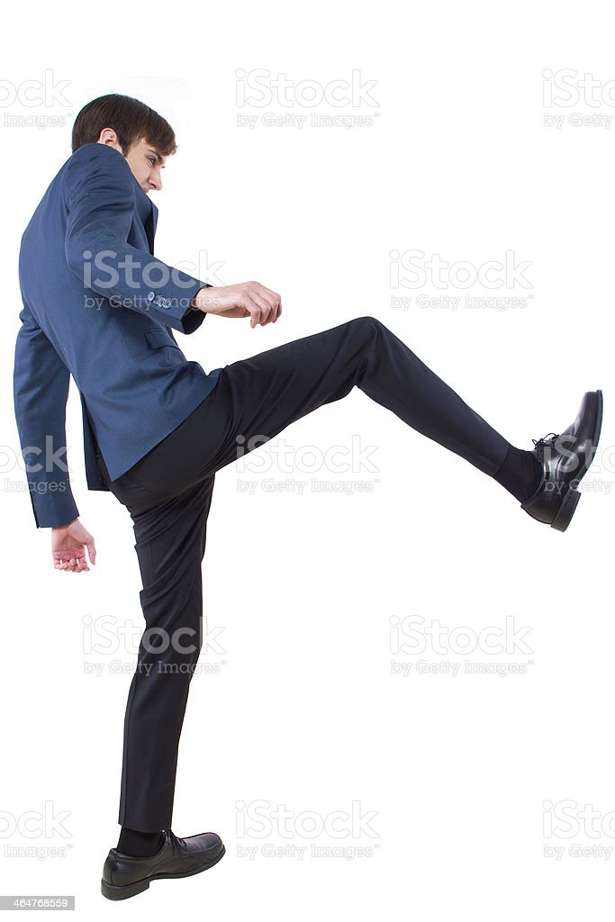 Young Businessman Kicking Something Imaginary stock photo
