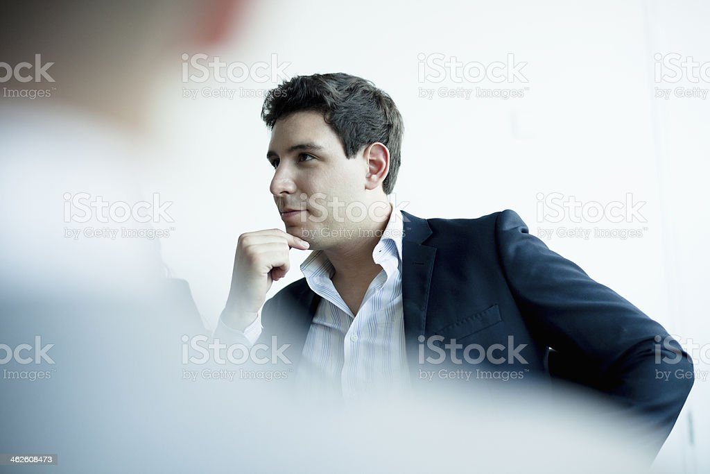 Young businessman listening in a business meeting stock photo