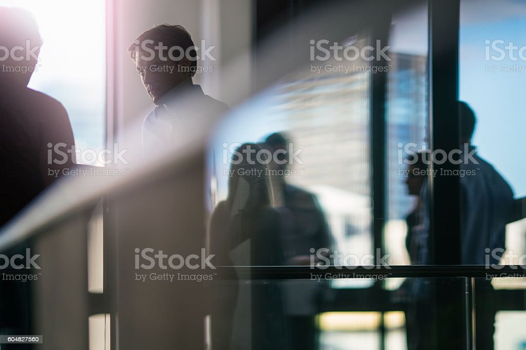 Young businessman looking at colleague stock photo