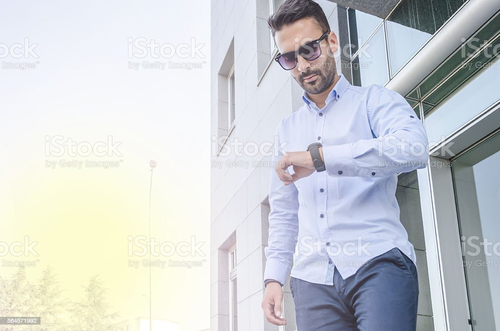 young businessman looking at his watch stock photo