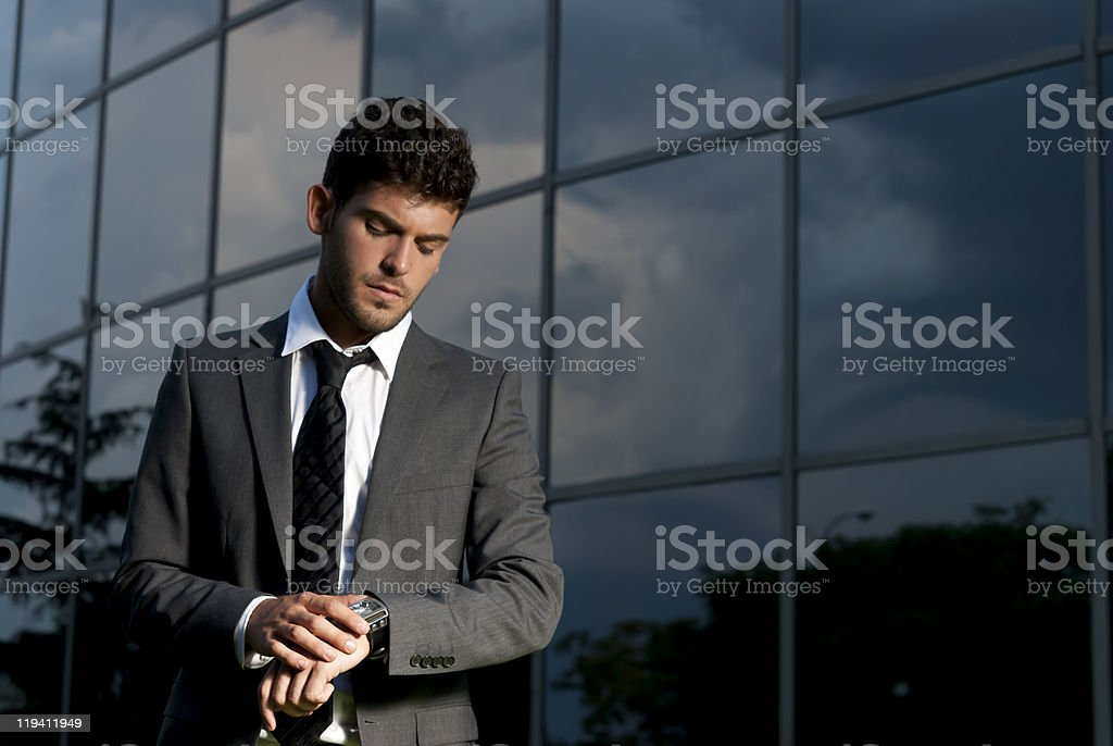 Young businessman looking clock at night on modern building background royalty-free stock photo