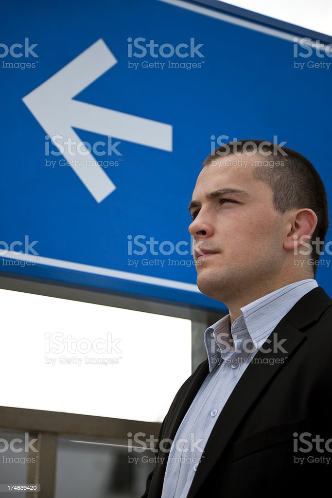 Young Businessman Looking in the Direction of Arrow, Business Concept royalty-free stock photo