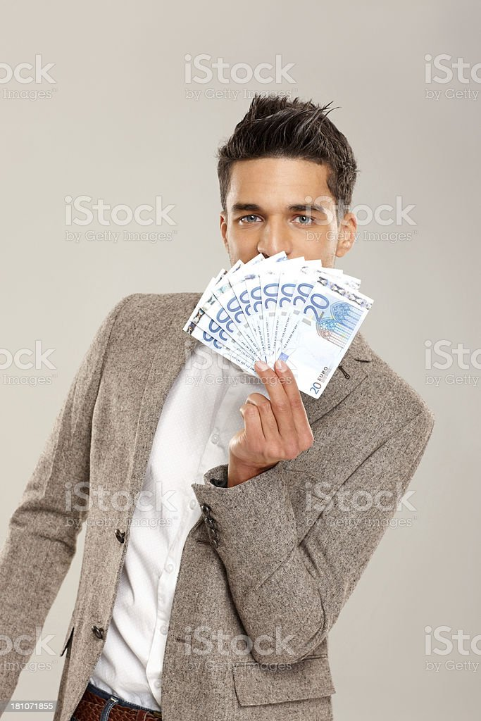 Young businessman looking through a fan of money royalty-free stock photo
