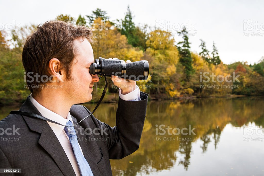 Young businessman looking through binoculars with autumn lake background stock photo