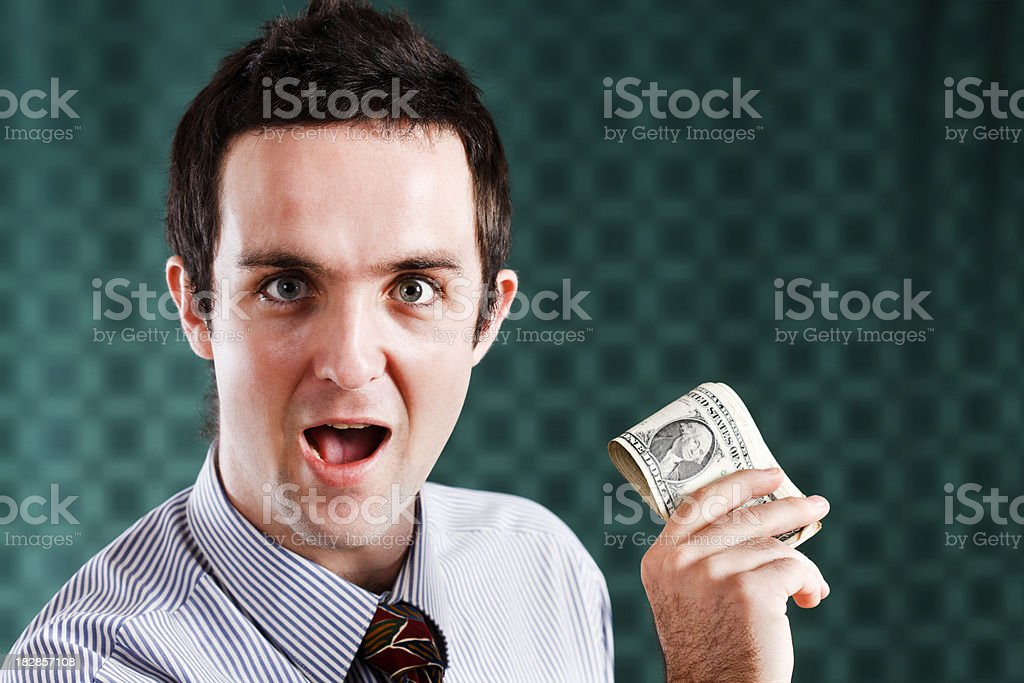 Young businessman looks happily amazed by money he's holding royalty-free stock photo