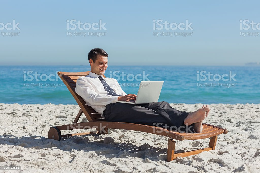 Young businessman lying on a deck chair with his laptop stock photo