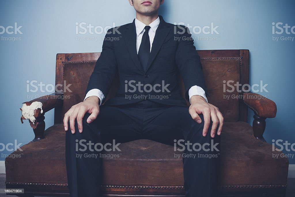 Young businessman on sofa in powerful pose royalty-free stock photo
