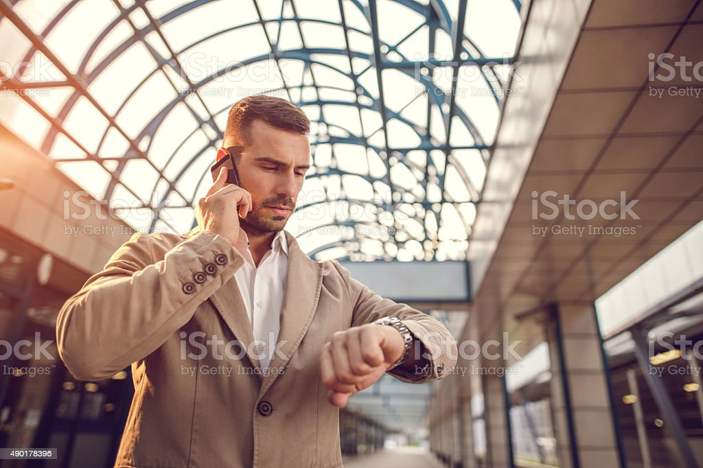 Young businessman on the phone checking the time. stock photo