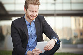 Young businessman outdoors using tablet pc