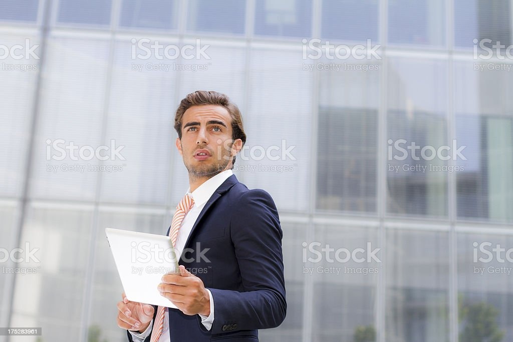 Young businessman outside office holding tablet royalty-free stock photo