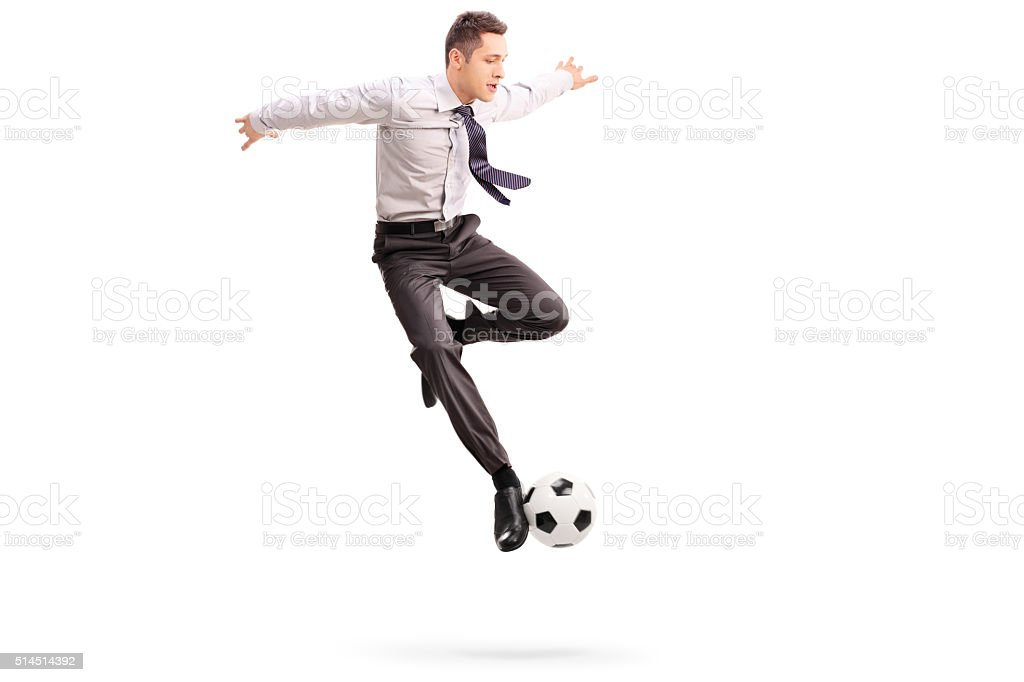 Young businessman playing football stock photo